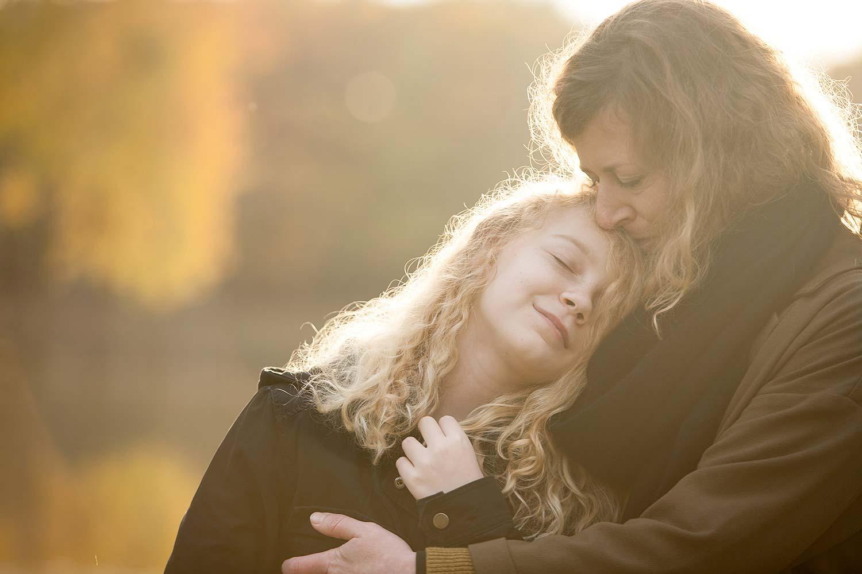buitenshoot van moeder en dochter knuffelend in de natuur