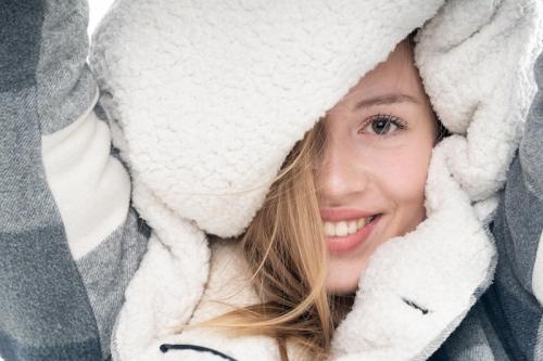 portretshoot van lachend meisje met sweater over haar hoof