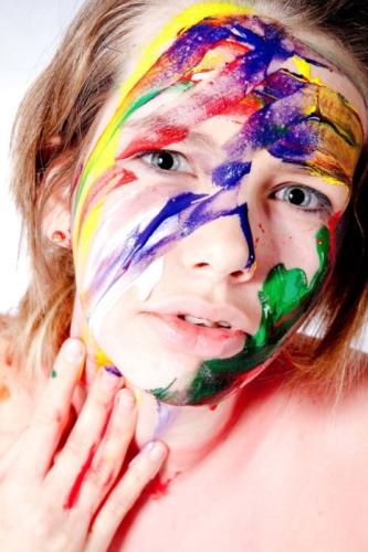 portretfoto met verf van meisje tijdens studioshoot